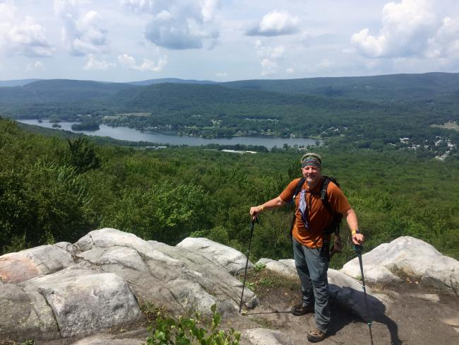 A man poses at a trail lookout