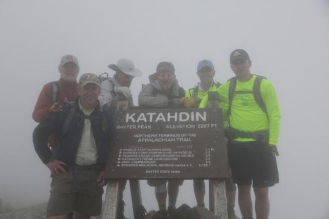 Six men stand behind a sign announcing the summit of Mt. Katahdin