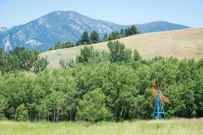 A windmill sculpture in front of trees and mountains