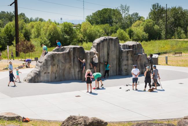 People climb on a constructed climbing boulder