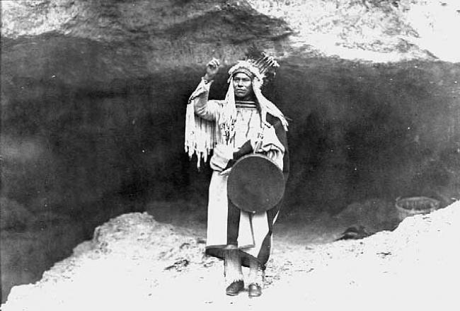 A Dakota man stands at the mouth of a cave in an old photo