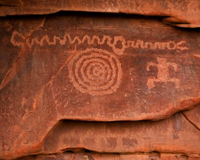 A rock art panel with a squiggly line, a human figure, and a spiral