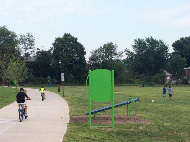 Photo of a kid riding a bike in a park  Photo of a kid riding a bike in a park