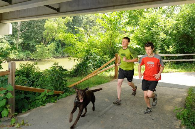 Two men jog with a dog along the South Chickamauga Creek Greenway in Chattanooga.  Two men jog with a dog along the South Chickamauga Creek Greenway in Chattanooga.