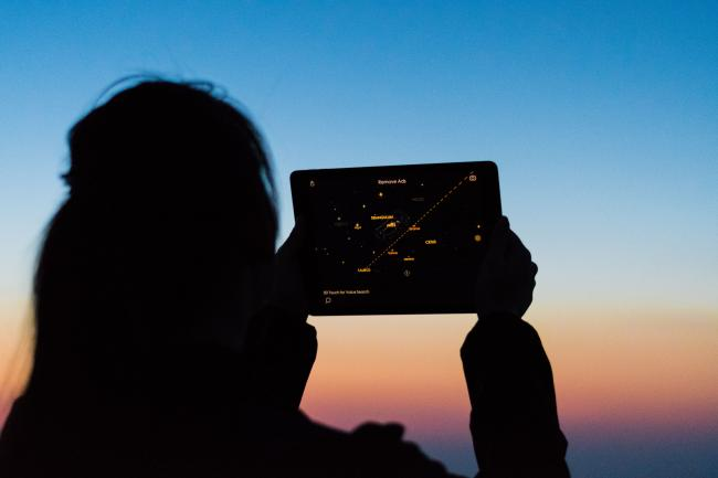 A woman looks at the sky using a star app on a tablet