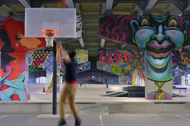 Photo of someone playing basketball with murals in the background  Photo of someone playing basketball with murals in the background