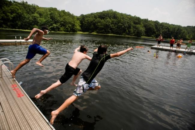 Boys jump from the swimming platform into the lake at Pouch Camp on Staten Island, NY.