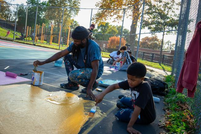 A school-aged boy paints a mural on the surface of a basketball court with help from a young man.