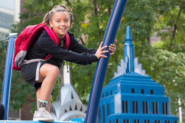 A girl wearing a backpack from L.L.Bean climbs a playground