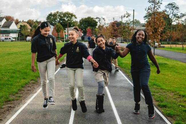 Four girls skip on a track holding hands