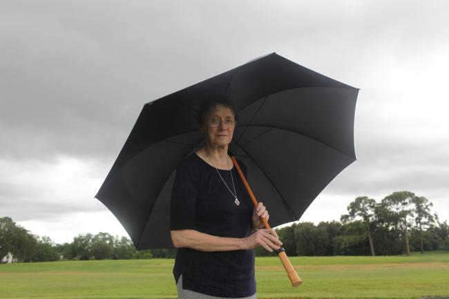 A woman holds an umbrella