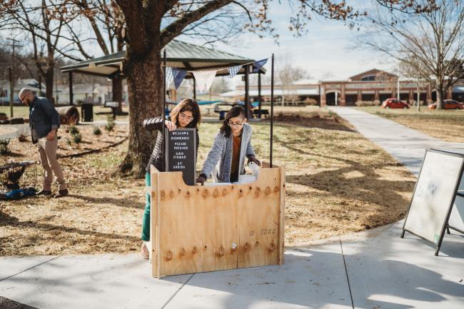 Two people at a booth in a park