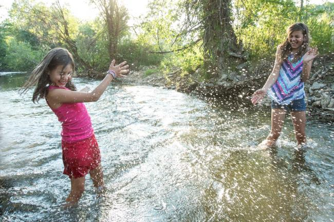 Kids play in a stream at Storymill Park
