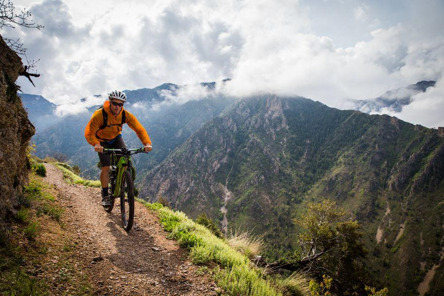 A man bikes on a trail on a mountain