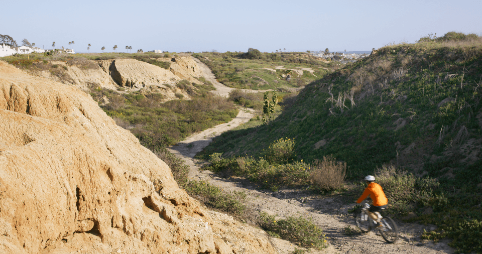 A person rides a bike on a gravel path at Banning Ranch
