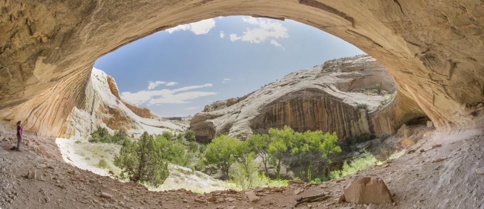 A person stands under an arch at Bears Ears National Monument