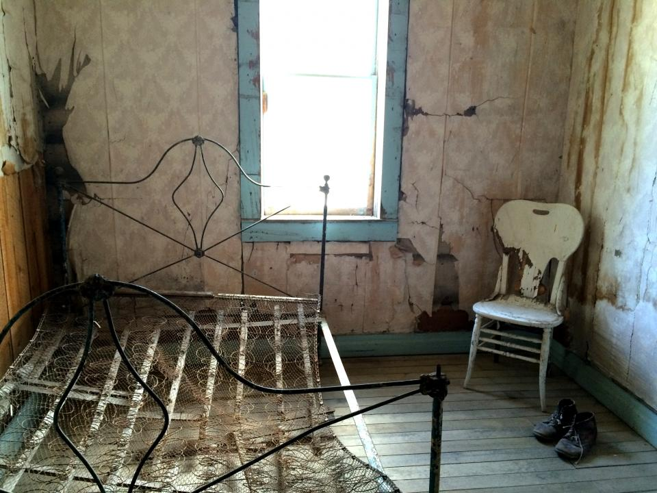 A rusty bedspring in an abandoned room