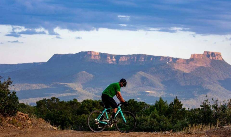 Juan De La Roca rides a mountain bike with Fisher's Peak in the background