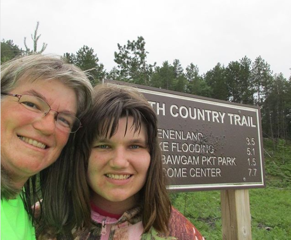 Laurie and Andrea Kass take a selfie by a North Country Trail sign