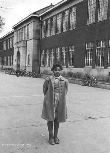 A young woman stands in front of a brick school