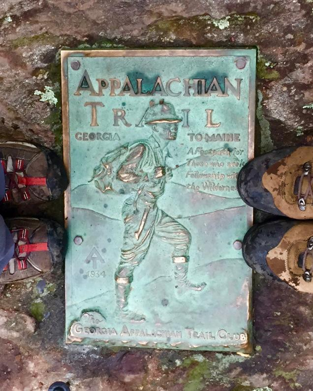 Two sets of boots stand on a plaque announcing the southern end of the Appalachian Trail