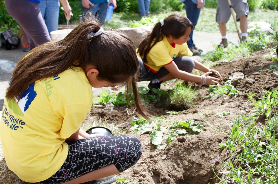 Girls planting at Creekside Experience event in Littleton, Colorado.