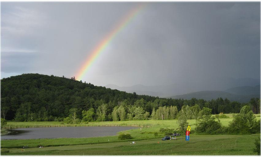 A rainbow over a green field with a mountain in the background