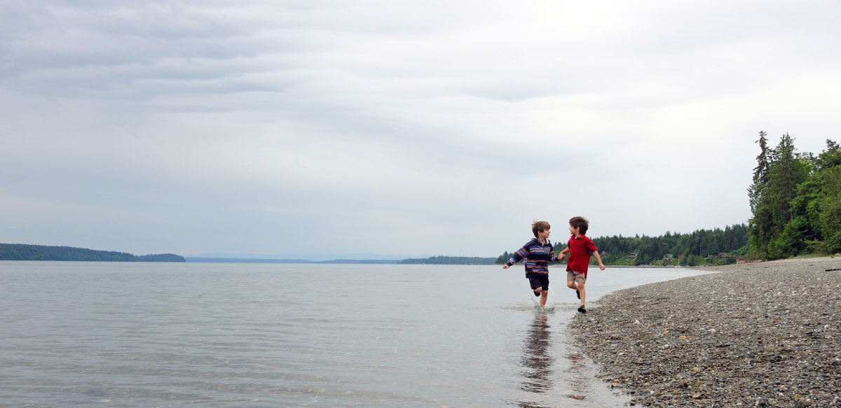 Two little boys run along the shore at Fudge Point, Puget Sound, WA
